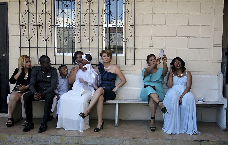 In this May 5, 2018 photo, brides and their guests sit on a bench in a parkin...