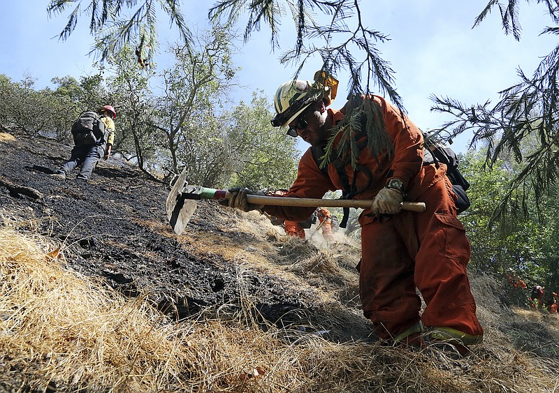 Firefighters clear burned and unburned brush from a hillside above Portola Dr...