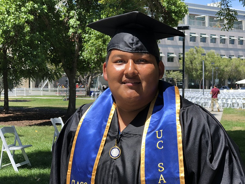 Leon Sanchez Reyes poses for a photo in his cap and gown at UC San Diego, Jun...