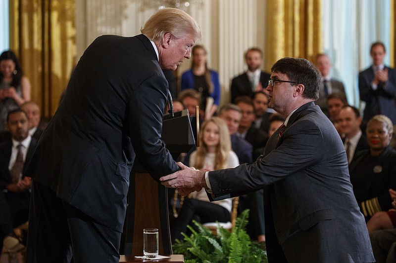 President Donald Trump shakes hands with acting Department of Veterans Affair...