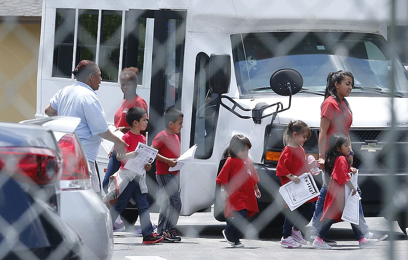 Migrant children walk off a bus at the Catholic Charities' Msgr. Bryan Walsh ...