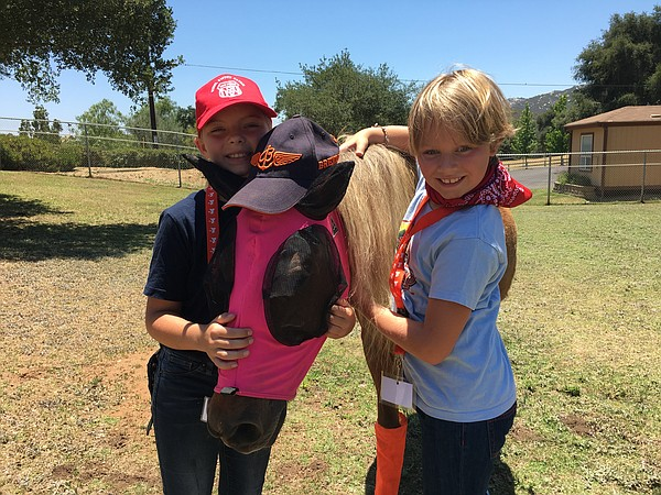 Grace Barnes and Heidi Bossart snuggle a miniature horse ...