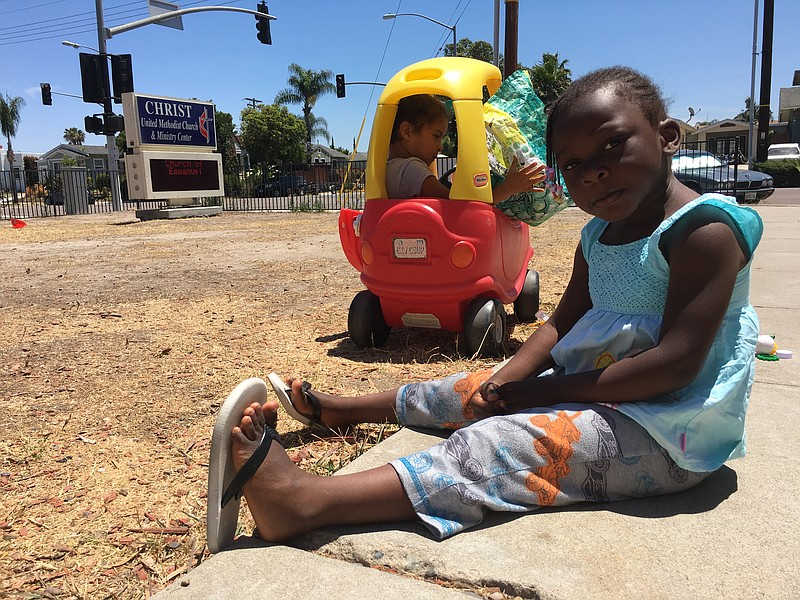 Hadidja Fousseni, 3, waits her turn to play in the donated Little Tikes car w...