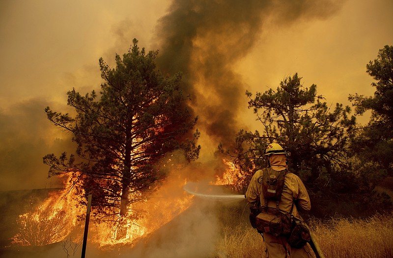 A firefighter scrambles to stop the Pawnee fire as it spots across Highway 20...