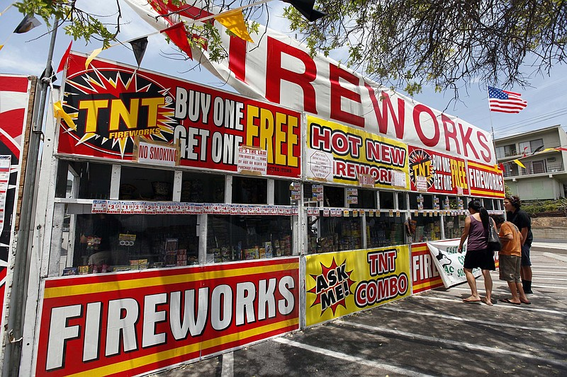 A family buys fireworks at a TNT Fireworks stand in the City of Monterey Park...
