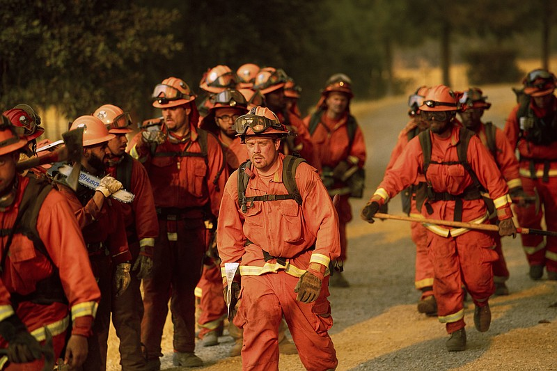 Inmate firefighters leave an assignment while battling a wildfire in Guinda, ...