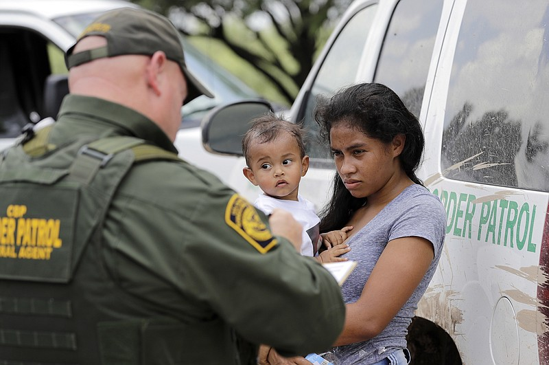 A mother migrating from Honduras holds her 1-year-old child as surrendering t...