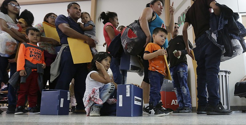Immigrant families seeking asylum wait in line at the central bus station aft...