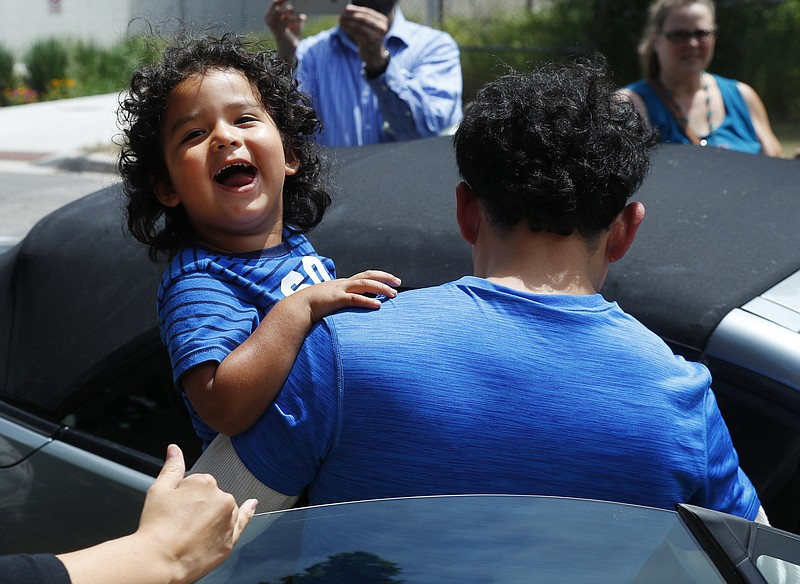 Ever Reyes Mejia, of Honduras, carries his son to a vehicle after being reuni...