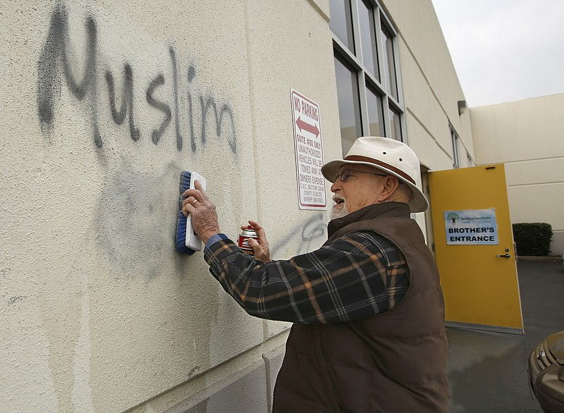 Tom Garing cleans up racist graffiti painted on the side of a mosque in what ...