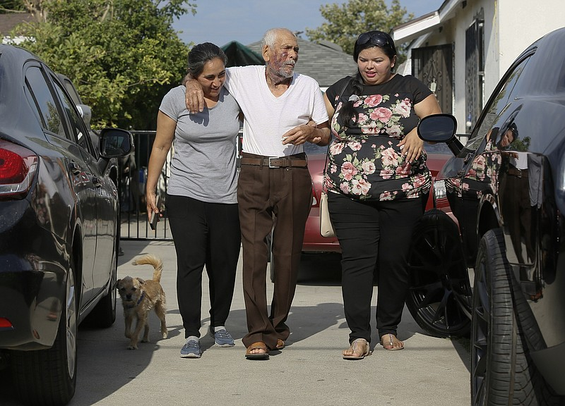 Aurelia Rodriguez, left, helps her father, Rodolfo Rodriguez, 92, center, wit...