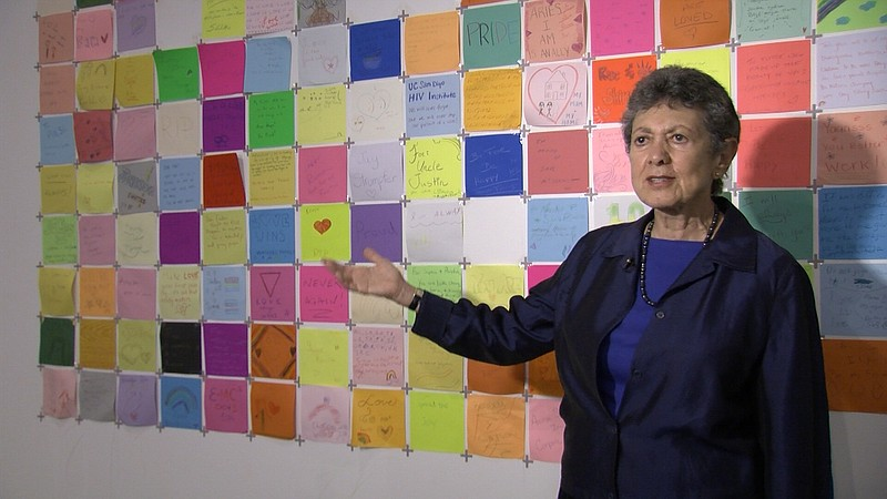 Curator Lillian Faderman stands next to the community quilt at the San Diego ...