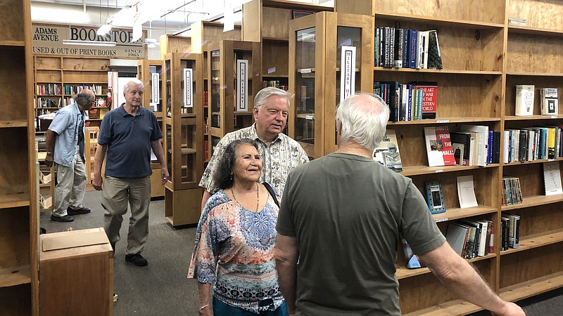 Customers make last-minute purchases at the Adams Avenue Book Store before it...
