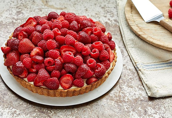 A red fruit tart piled high with colorful berries.
