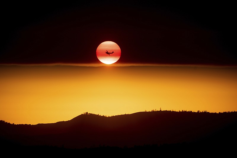 A plane battling the Ferguson Fire passes the setting sun in unincorporated M...