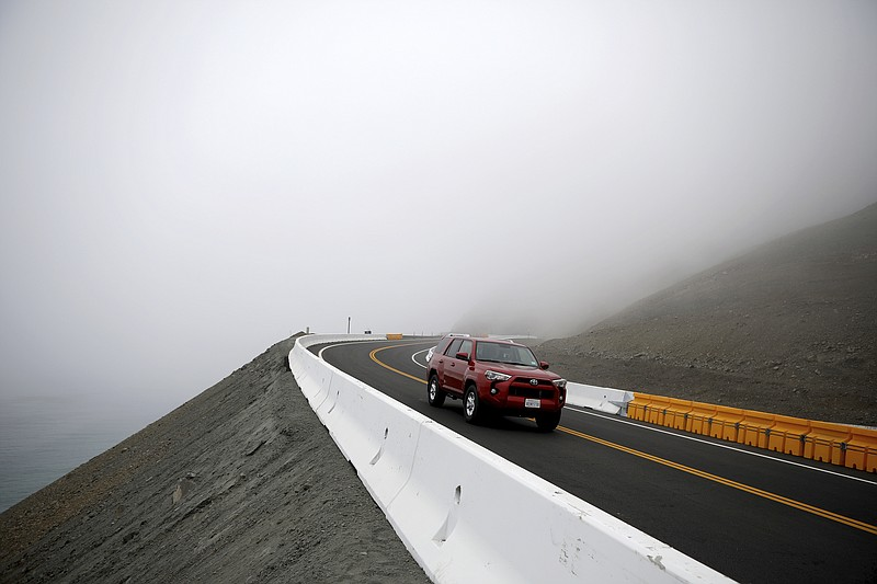 An SUV drives on the newly opened section of Highway 1 along the coast near B...