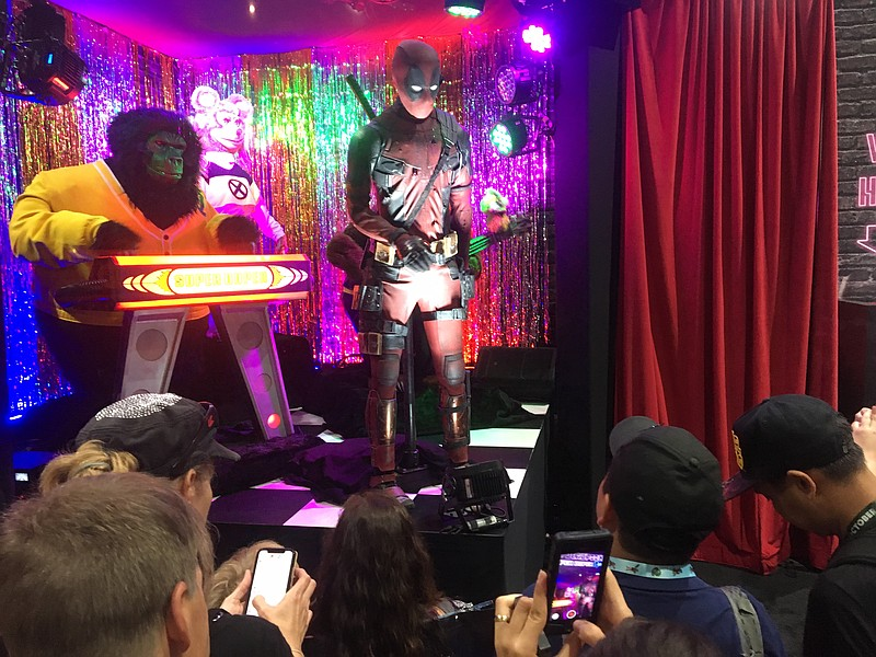 San Diego Comic-Con attendees watch a short music show at the Deadpool 2 boot...