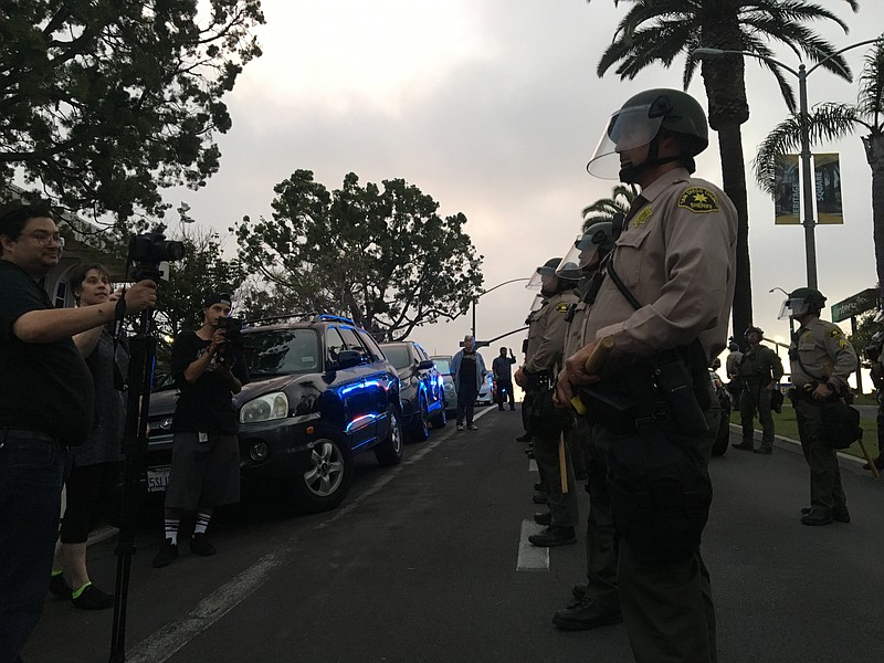 Police in riot gear line the street in National City outside a city council m...
