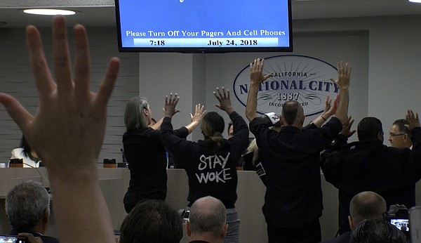 Protesters interrupt a city council meeting in National C...