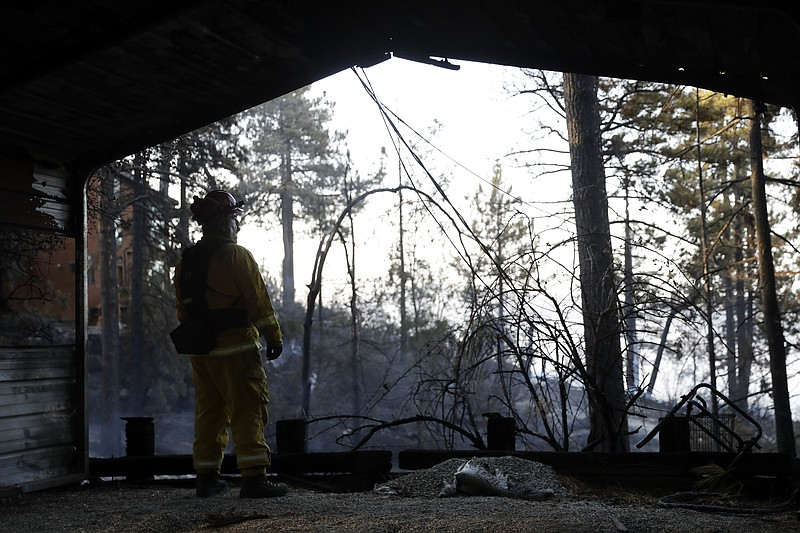 A firefighters looks out from inside a burned down property in Idyllwild, Cal...