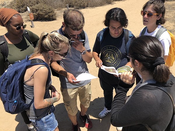 UC San Diego students look at clues for a scavenger hunt,...