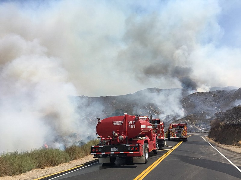 Fire trucks working to extinguish flames from the Pasqual Fire in San Pasqual...