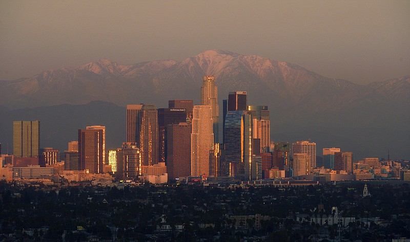 The sun sets over downtown Los Angeles skyline with the snow covered mountain...