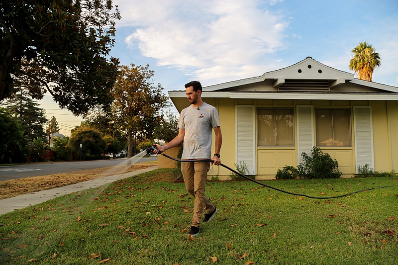 Brandon Miller waters the lawn in front of his Riverside home, July 17, 2018.