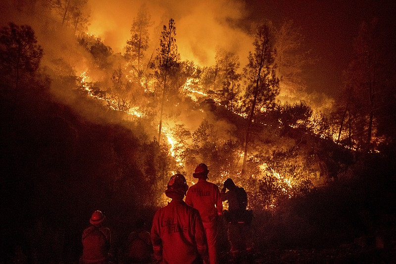 Firefighters monitor a backfire while battling the Ranch Fire, part of the Me...