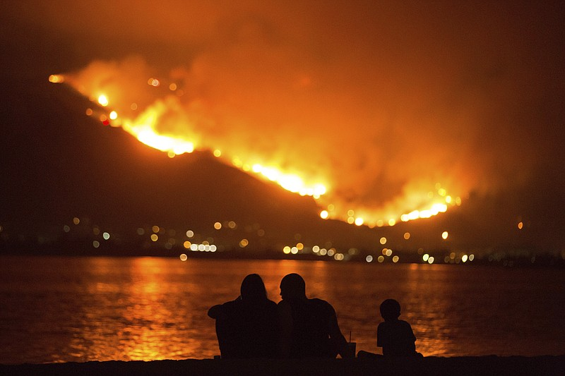 A family sits along the shore of Lake Elsinore as they watch the Holy Fire bu...