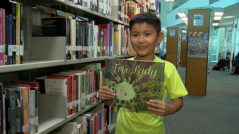 Nine-year-old Timothy Tang holds up his favorite book, Tree Lady, at the City...