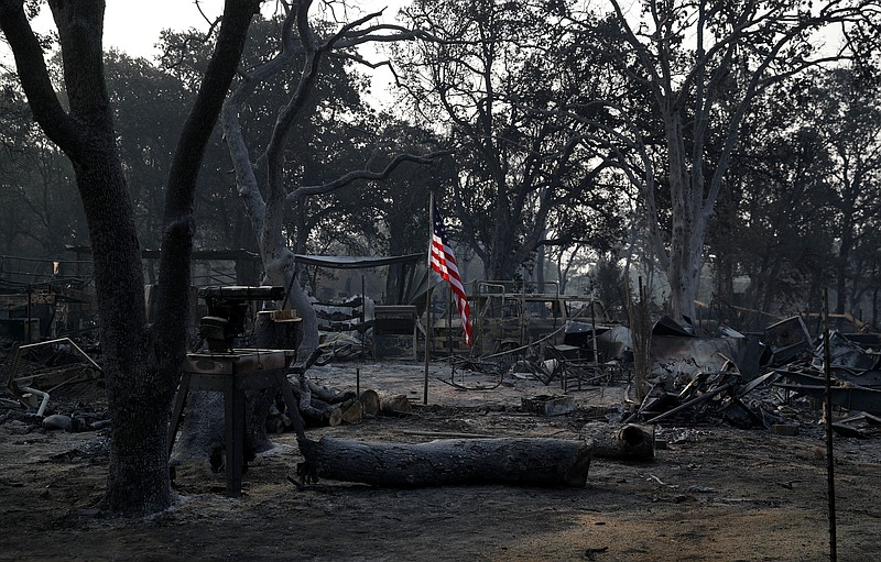A flag flies in the charred rubble of a home burned in the Carr Fire, Saturda...