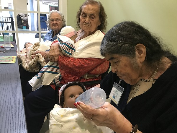 Women hold therapeutic baby dolls at the clinic at Glenne...