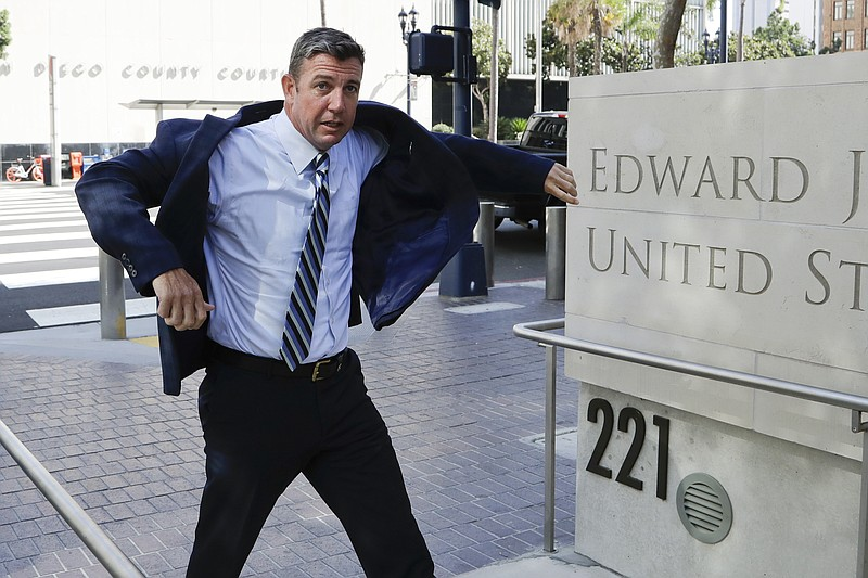 U.S. Rep. Duncan Hunter pulls on his coat as he arrives for an arraignment he...