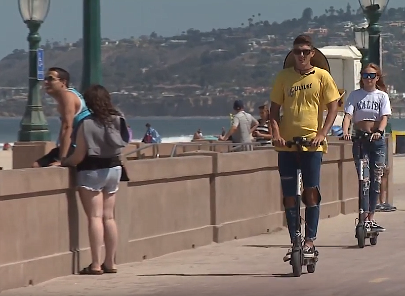 People ride electric scooters on the Mission Beach boardwalk, July 3, 2018.