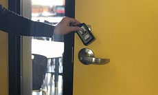 Shawn Loescher uses a key card to access a clas...