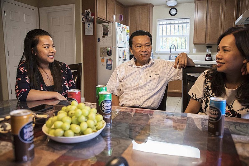 Jenny Nguyen, with her parents Khanh Nguyen and Tammy Vo, sitting in their ho...