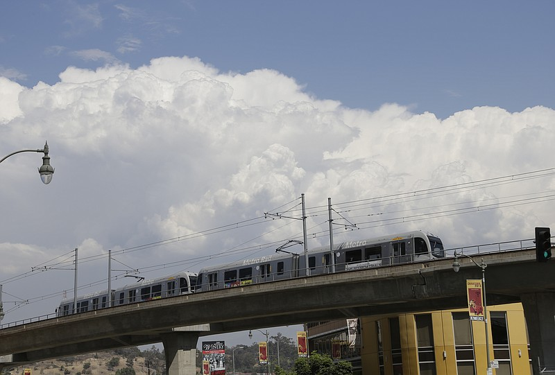 Thunderhead cloud formations are seen over the Metro Rail on the Metro Gold l...