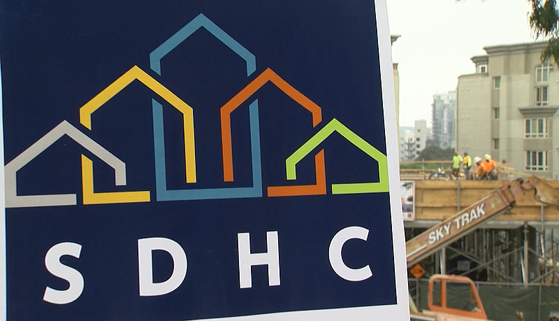 The San Diego Housing Commission logo is seen in front of the construction si...