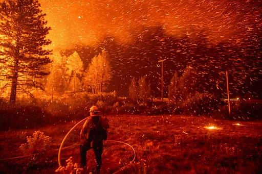 Embers fly above a firefighter as he works to control a backfire as the Delta...