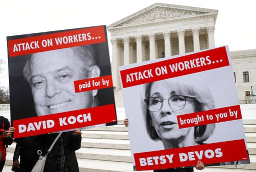Members of the American Federation of Teachers hold up signs depicting Educat...