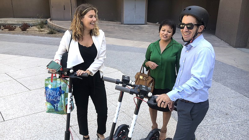 Three people stand by Bird electric scooters near Civic Center Plaza downtown...