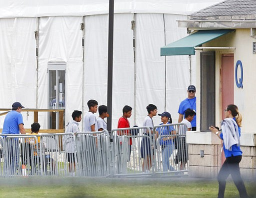 Immigrant children walk in a line outside the Homestead Temporary Shelter for...