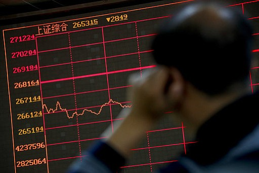 An investor monitors shares prices in front of an electronic board displaying...