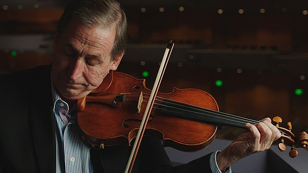 Roger Frisch plays the violin after turning on the electr...