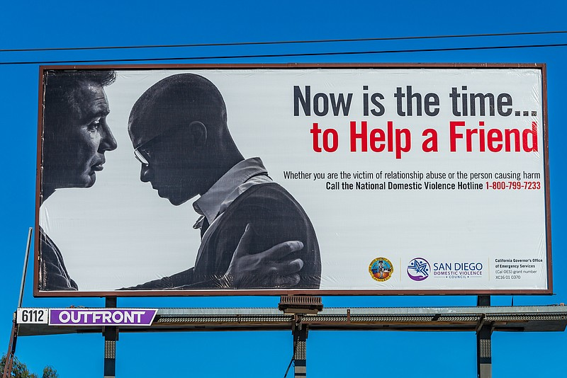 A domestic violence campaign billboard reads