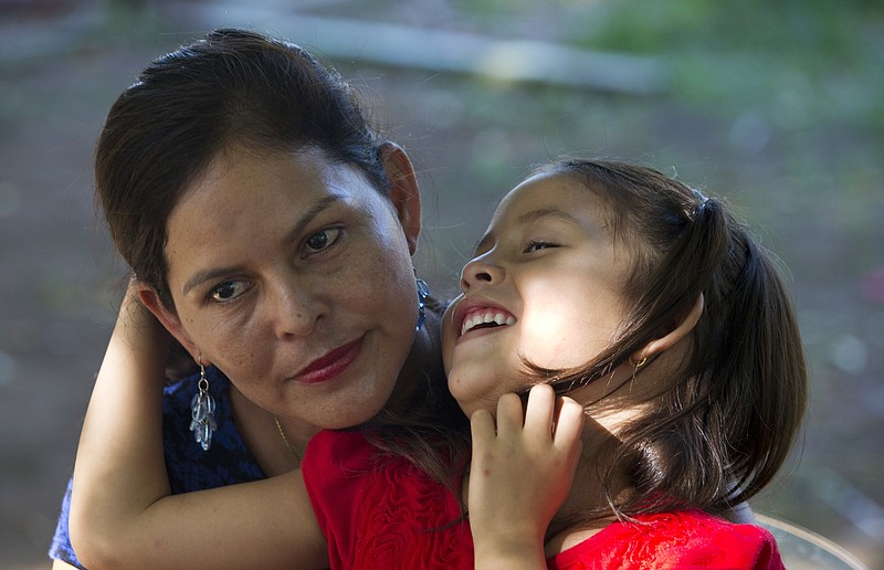 Araceli Ramos holds her 5-year-old daughter, Alexa, on her lap during an inte...