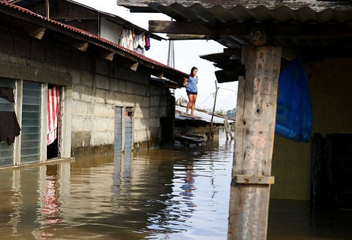 A resident stands on the roof of her house amidst flooding brought about by T...