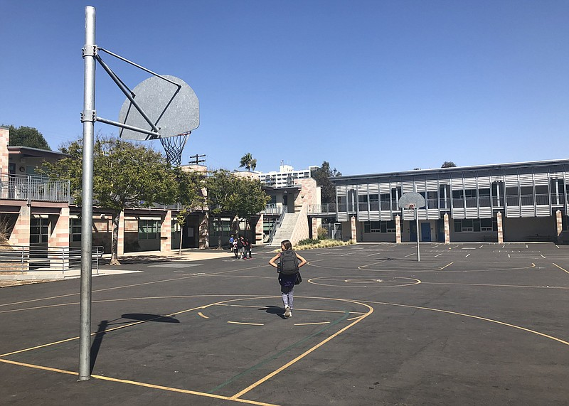 Students walk across the basketball courts at Grant Elementary School in the ...