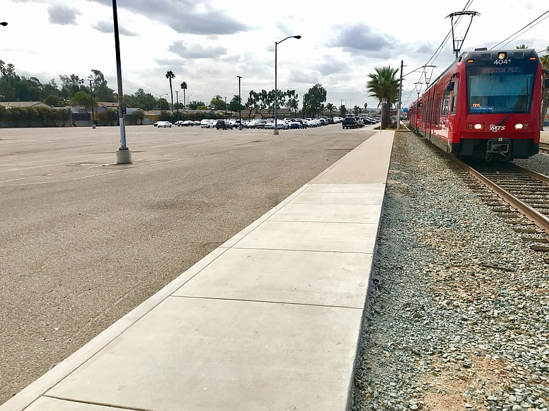 An MTS trolley car passes by a mostly empty parking lot at the Palm Avenue st...